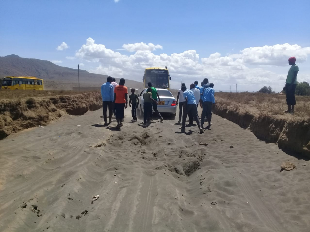 Students pushing aside a vehicle stuck in the sand
